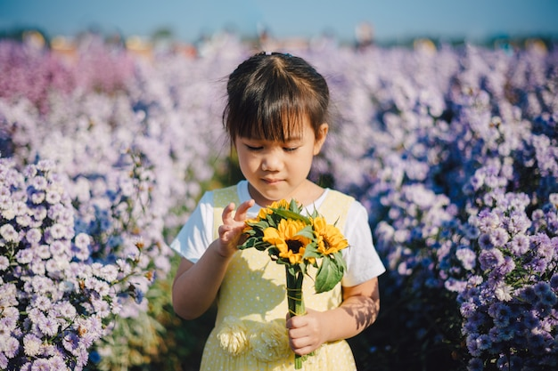 Asian kid exploring natural environment in the flower garden