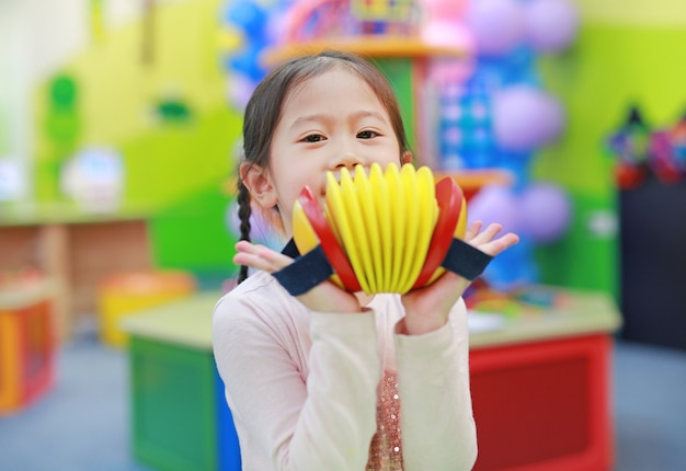 Asian kid girl having fun with toys, musical instruments.