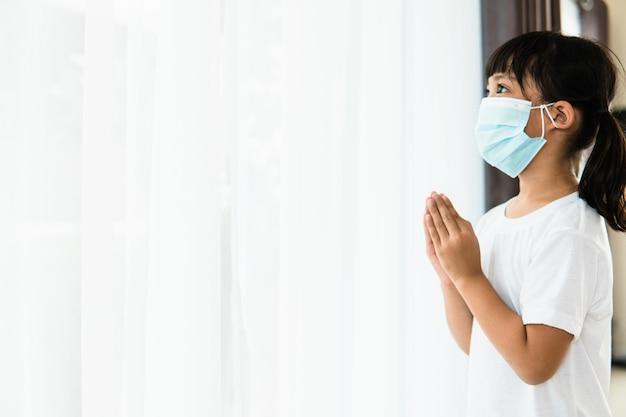 Азиатская девочка молится в маске для защиты pm2.5 и covid-19 маленькая девочка молится за руку