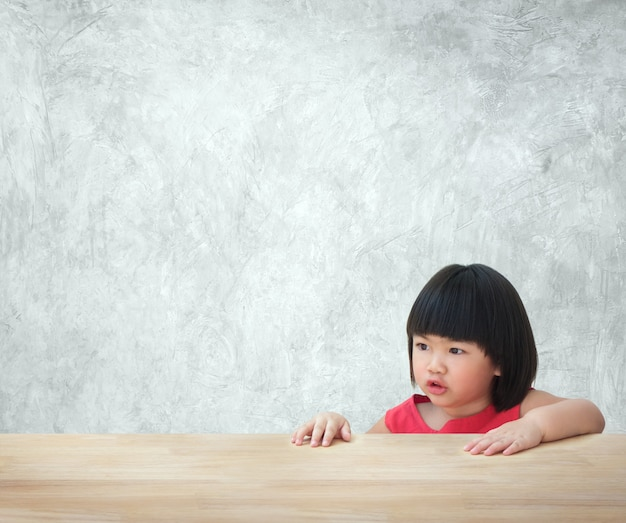 Asian kid girl sitting behind empty table with concrete wall