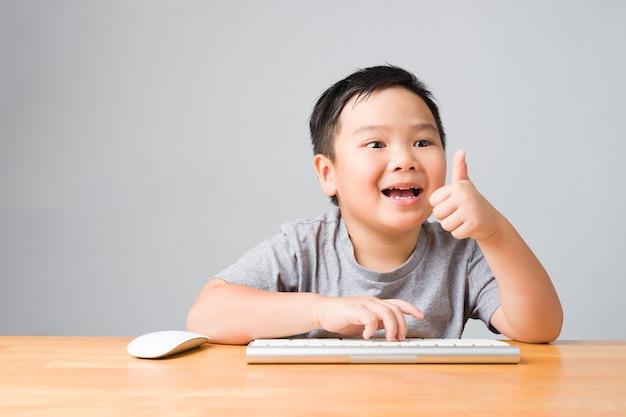 Азиатский ребенок / счастливый ребенок улыбается и использует клавиатуру и мышь, соглашается с изучением онлайн-уроков. концепция онлайн-обучения и самообучения.