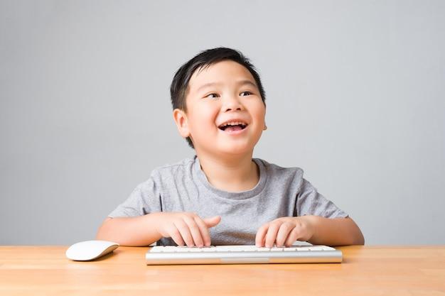 Азиатский ребенок / счастливый ребенок улыбается и с помощью клавиатуры и мыши изучает онлайн-уроки. концепция онлайн-обучения и самообучения.