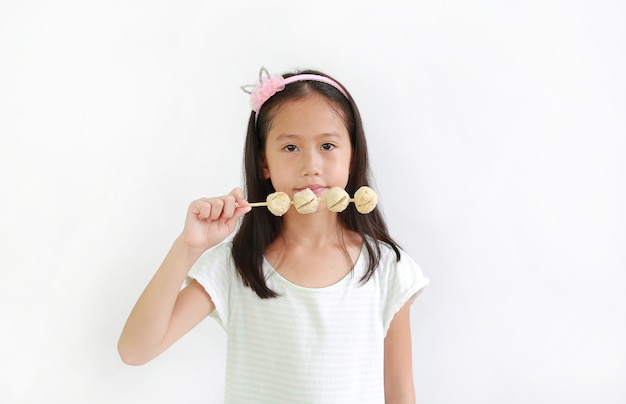 Asian kid holding meat ball stick over white background. portrait of little girl child eating meatball with looking at camera