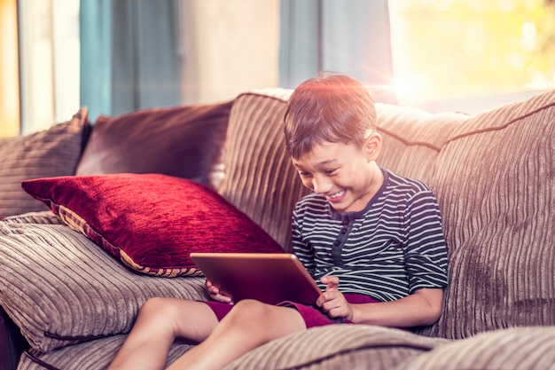 Asian kid holding and playing on his  tablet device sitting on sofa with pillow, smiling joyfully enjoying free time, sunset jour with light shining in living room, wearing short and stripy shirt