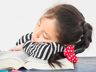 Asian kid is sleeping while reading a big book