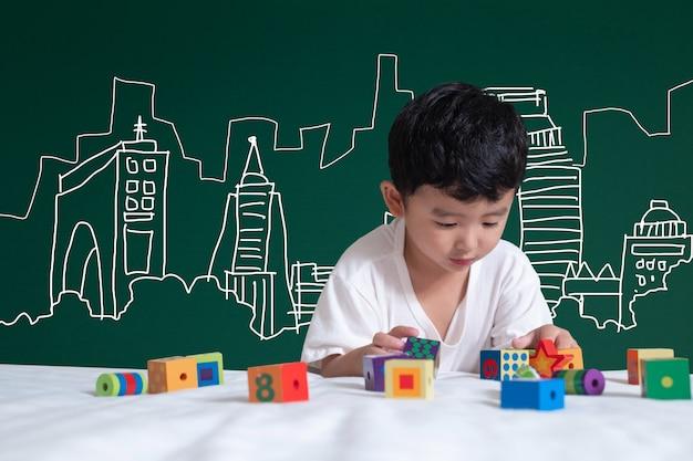 アジア人の子供が建築とエンジニア建築のデッサンとデザイナーについての彼の想像力で遊ぶことによって学ぶこと