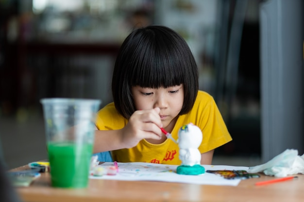 Asian kid paint color on paper, education concept