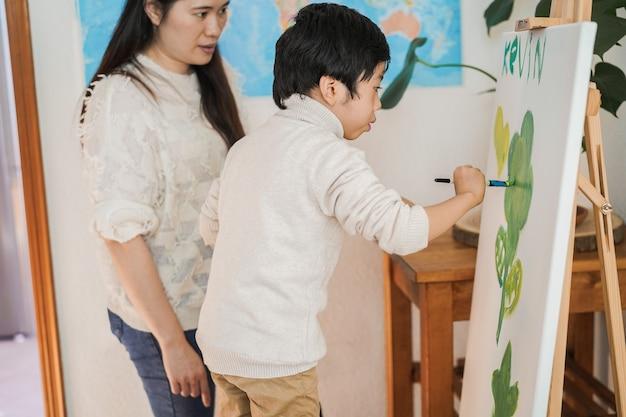 Азиатский ребенок рисует на холсте во время урока рисования дома - сосредоточьтесь на лице маленького мальчика