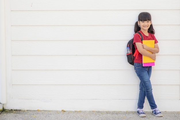 Asian kid schoolgirl student wears uniform and face mask for coronavirus protection safety holding backpack stands isolated on white background looking at the camera, portrait.