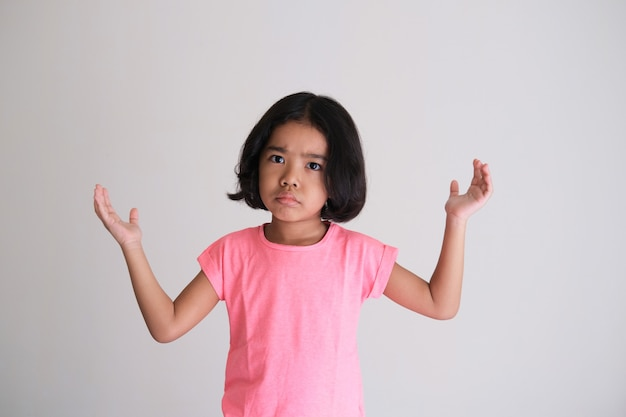 Asian kid showing annoyed face expression with her hands raised