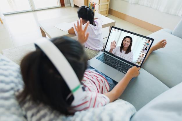 ソファに座って、ワークシートをしている姉妹と一緒に先生やクラスグループとビデオ会議チャットをしているアジアの子供はそばにいます。 covid-19の発生により、子供たちは検疫中に自宅から勉強します。