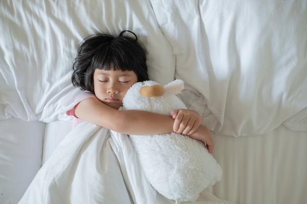 Asian kid sleep on bed, sick child