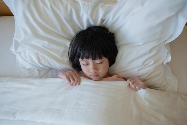 Азиатский ребенок спит на кровати, больной ребенок Premium Фотографии