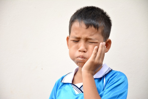 Asian kid suffering from toothache pain holding his cheek