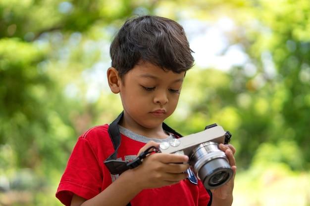 Азиатский ребенок фотографирует в общественном парке с помощью цифровой камеры