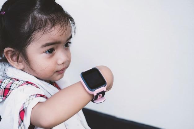 アジアの子供は幸せそうな顔でテクノロジースマートウォッチを使用しています。