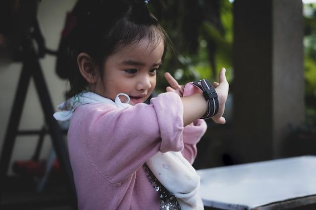 アジアの子供は幸せそうな顔でテクノロジースマートウォッチを使用しています