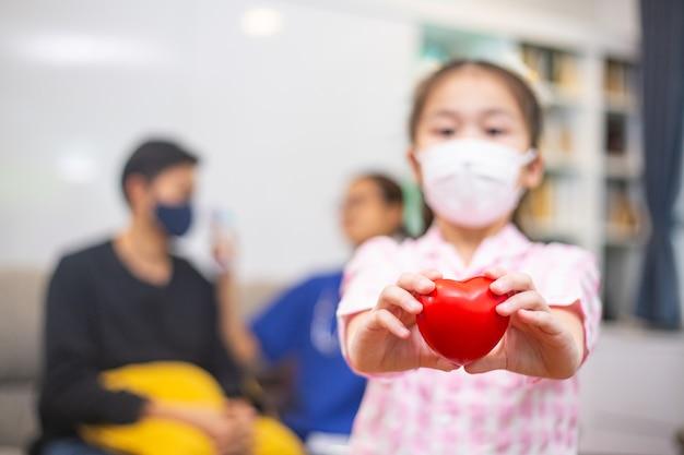 アジアの子供はマスクを着用し、愛のシンボルを与え、あなたの健康をケアするためにポンプ読み取りハートを保持します