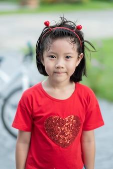 Азиатский ребенок с размытым фоном, счастливая девушка