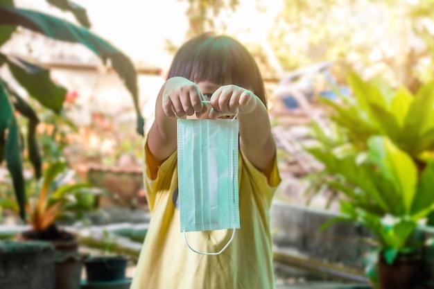 Азиатский ребенок с маской для защиты от вируса и уменьшения распространения коронавируса (covid-19), выборочный фокус