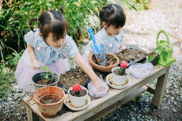 식물을 심는 아시아 아이들. 지구의 날에 대한 개념과 행성의 자연을 구하십시오.