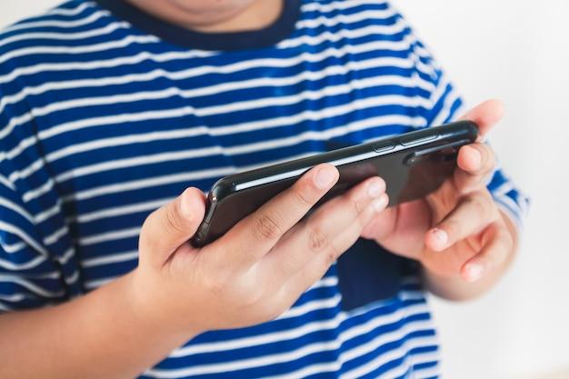 아시아 어린이들이 스마트 폰에서 게임을합니다.