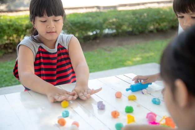 アジアの子供たちは、遊びを通して学び、粘土の成形形状で遊ぶ
