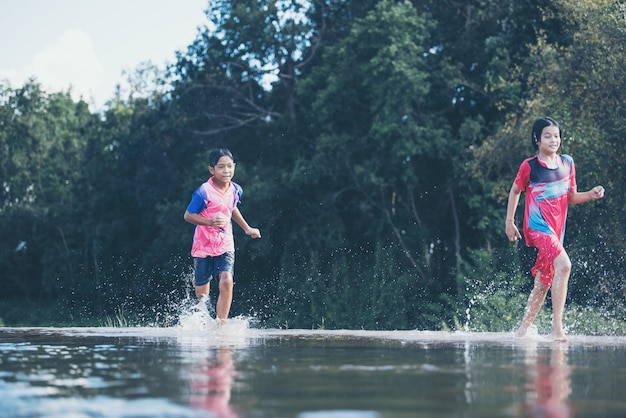 Asian kids playing in a river