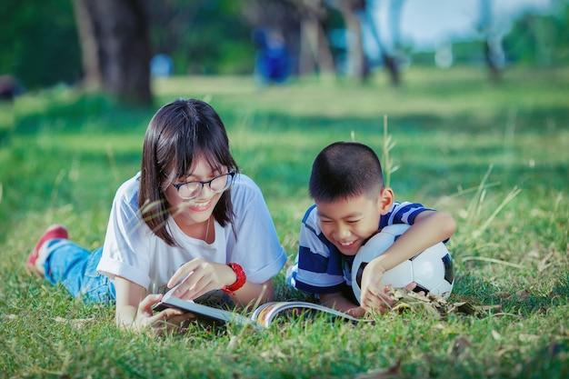 公園でアジアの子供たちの読書