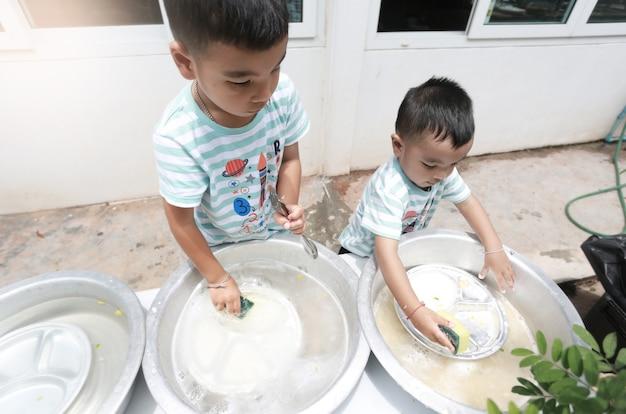 아시아 아이들은 함께 설거지를 하고 집에서 즐거운 시간을 보내고, 홈스쿨링과 교육 개념을 가지고 있습니다.