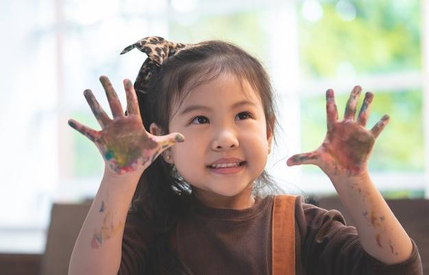 Asian kids with dirty painted hand in art classroom