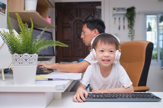 Asian kindergarten boy playing near his working at home father