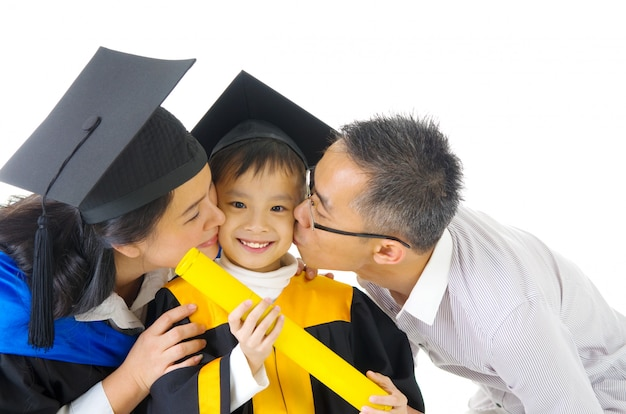 Asian kindergarten child in graduation gown and mortarboard kissed by her parent during graduation