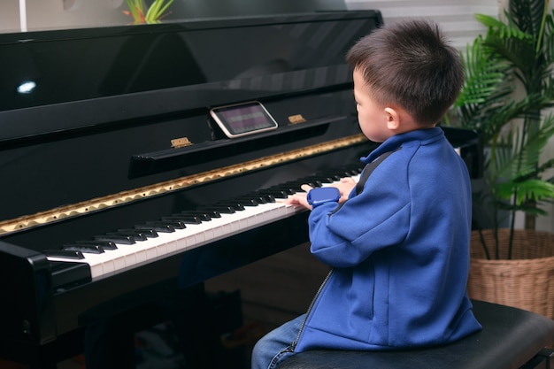 Asian kindergarten school boy child learning to play piano using smartphone with an online lesson and course in living room at home