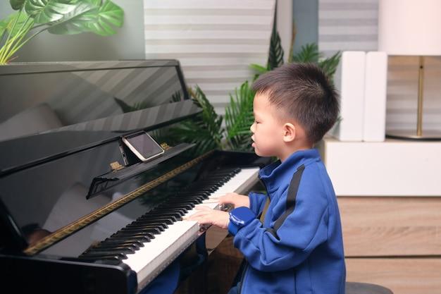 自宅のリビングルームでオンラインレッスンとコースでスマートフォンを使用してピアノを弾くことを学ぶアジアの幼稚園の男の子