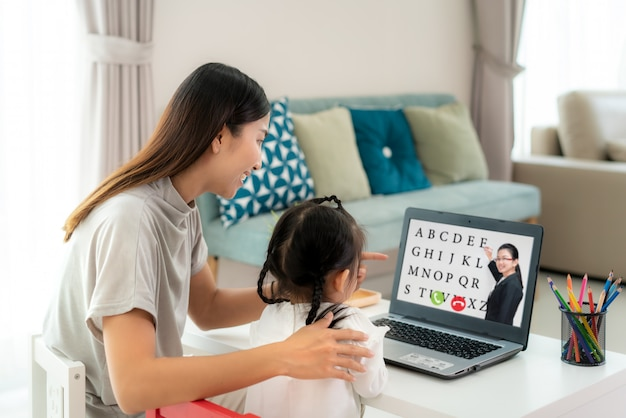 Asian kindergarten school girl with mother video conference e-learning with teacher on laptop in living room at home. homeschooling and distance learning ,online ,education and internet.