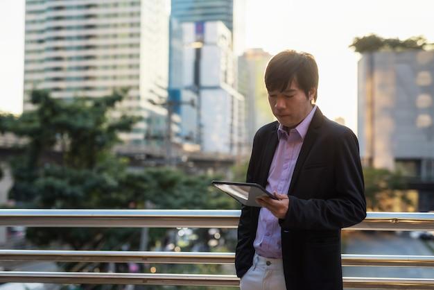 아시아의 40대 사업가는 도시의 일몰에 사무실 건물 밖에서 디지털 태블릿으로 회의 일정과 비즈니스 프로젝트 계획을 확인합니다. 현대 도시의 기업 응용 프로그램에서 작업합니다.