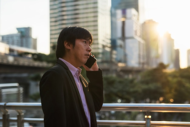 アジアの韓国人40代のビジネスマンは、都会の日没時にスカイウォールの歩道で歩いて電話で話します。町での輸送中の緊急の商談と会議。