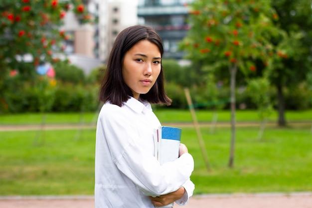 夏または秋の公園で屋外に立っているアジア、韓国または中国の大学生の女の子