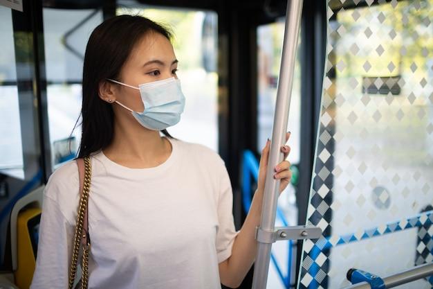 アジアの韓国人または日本人女性がフェイスマスク付きの公共交通機関のバスまたは路面電車に乗車