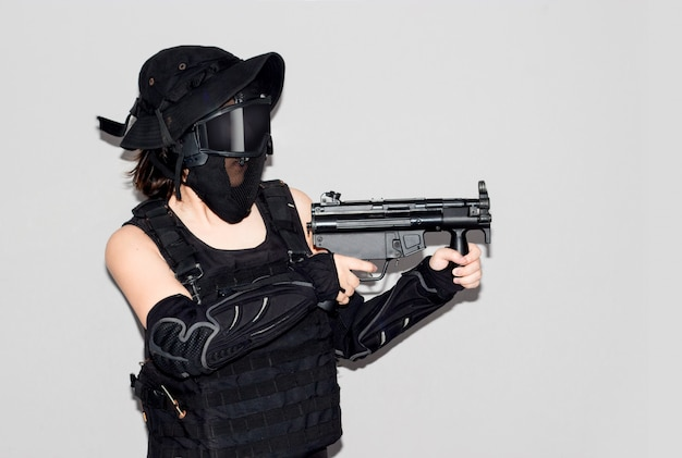 Asian lady in black soldier bb gun sport game costume and weapon