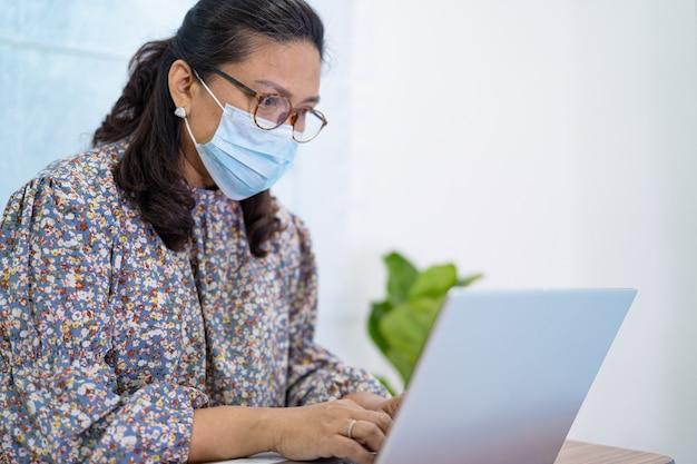 コロナウイルスを保護するためのマスクを身に着けているアジアの女性実業家