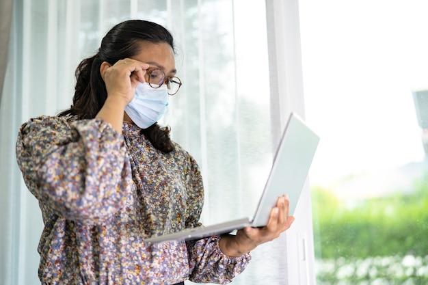 在宅勤務のアジア人女性実業家がノートパソコンで通信