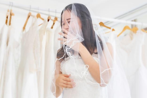 Asian lady choosing dress in a wedding shop.