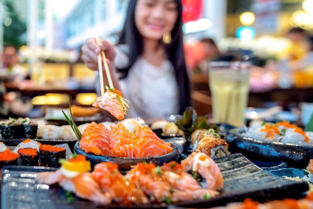 Азиатская дама ест лососевую рыбу, сашими и суши в японском ресторане
