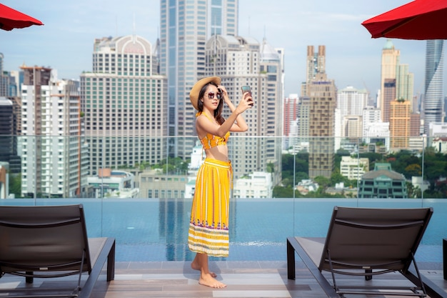 Asian lady enjoy selfie in swimming pool in rooftop of hotel in bangkok city, thailand