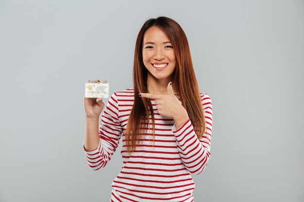 Asian lady holding credit card and pointing.