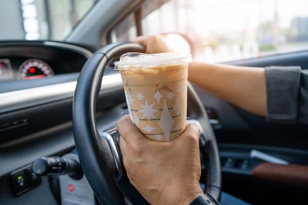 車の中で食べ物を飲むためにアイスコーヒーを保持しているアジアの女性。