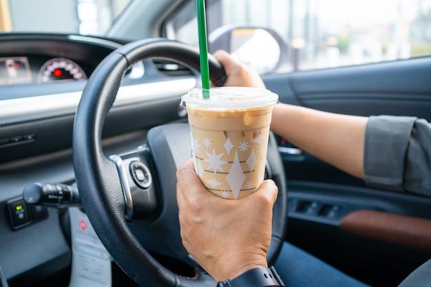 차에 아이스 커피를 들고 아시아 아가씨입니다.
