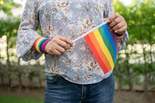 Lgbtプライド月間のシンボルであるレインボーカラーの旗を掲げるアジアの女性は、毎年6月にゲイ、レズビアン、バイセクシュアル、トランスジェンダー、人権の社会を祝います。